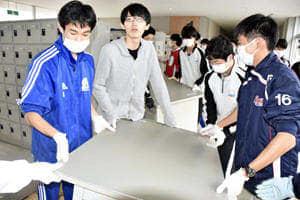 浸水の影響が残る校舎で机を搬入する生徒ら=24日午前10時15分ごろ、相馬市・相馬東高