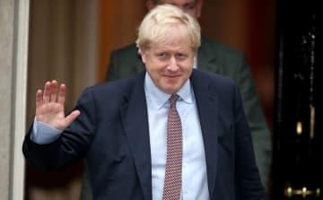 24日、英首都ロンドンで、首相官邸から姿を見せたジョンソン英首相(ロイター=共同)