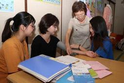 韓国人留学生の血圧を測る黒野利佐子准教授(右から2人目)と女子学生=神戸市兵庫区中道通2