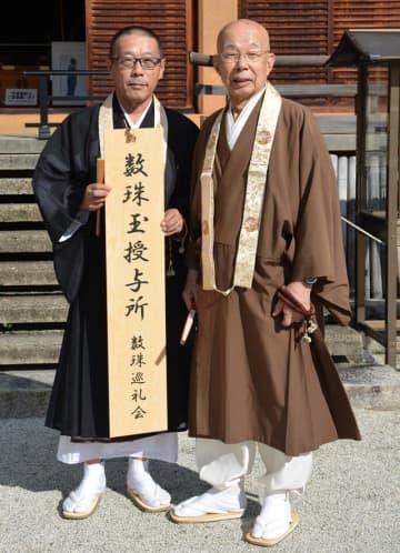 「数珠玉授与所」と書かれた看板を持つ数珠巡礼会の滋野事務局長(左)と宮城会長
