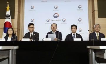 25日、ソウル市内で世界貿易機関(WTO)の優遇措置を受けられる発展途上国としての地位放棄を表明する洪楠基・経済副首相兼企画財政相(中央)ら(聯合=共同)