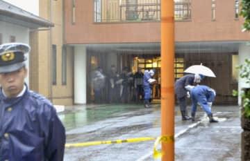 男性が首に刃物で刺されたようなけがを負った事件で、クリニック駐車場を調べる捜査員ら=25日午前9時10分、東京都新宿区市谷山伏町