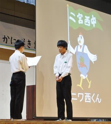 生徒会長の中谷さん(左)から表彰を受ける、マスコットキャラクター考案者の荒木さん