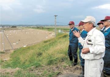 災害ごみが堆積した田んぼを視察する町議ら