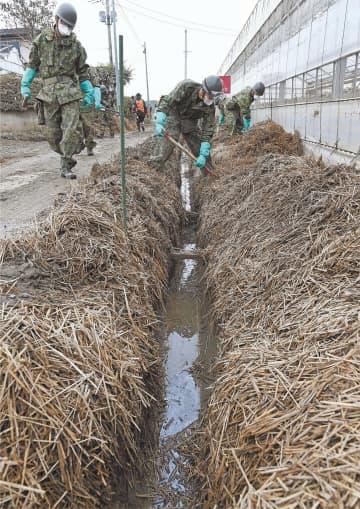 大雨に備え水路の稲わらを片付ける自衛隊員=25日午前10時30分ごろ、大崎市鹿島台大迫