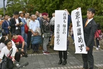 岩国基地騒音訴訟の二審判決で「差止認めず」などと書かれた紙を掲げる原告団関係者=25日午後、広島高裁前