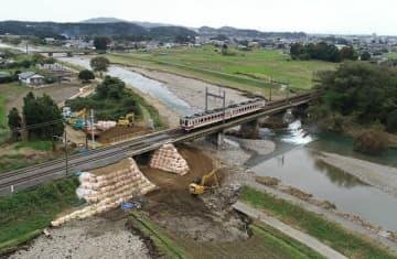 全線で運転を再開した東武日光線。北鹿沼-板荷駅間の鉄道橋は土のうを積むなどの復旧工事が行われた=24日午後0時20分、鹿沼市見野、小型無人機から