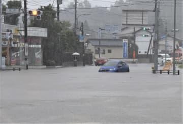 大雨により道路が冠水。車がハザードランプを点滅させ立ち往生した=25日午後1時10分ごろ、市原市の米沢交差点