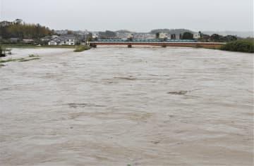 茶色い濁流により増水した養老川=25日午後3時15分ごろ、市原市の西広橋付近