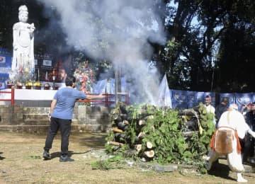護摩をたいて戦没者を追悼する参列者(左)ら=25日、フィリピン・マバラカット(共同)