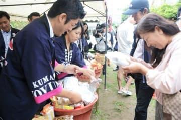 神事の後、みそを配る県みそ醤油工業協同組合のメンバー(左側)=熊本市中央区