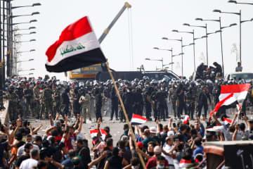 25日、イラクの首都バグダッドで、デモ参加者の前に立ちはだかる治安部隊(ロイター=共同)