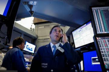 ニューヨーク証券取引所のトレーダー=25日(ロイター=共同)