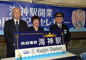 新しい駅名看板で海神駅の開業100年を祝う川瀬駅長(右)ら=25日、同駅前