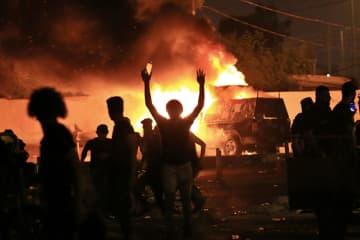25日、イラク南部バスラで、警察車両を燃やす反政府デモ隊(AP=共同)