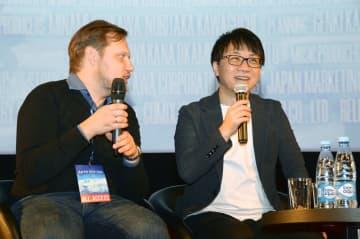 26日未明、モスクワの映画館でロシア人ファンの質問に答える新海誠監督(右)(共同)