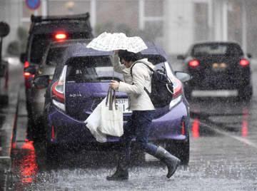 強い風雨の中を急ぎ足で歩く人=25日午後1時22分、千葉県佐倉市