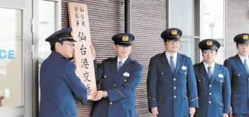 開所した仙台港交番に看板を掲げる高橋所長(左から2人目)ら