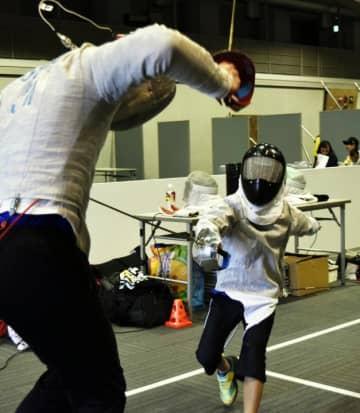 フェンシングの防具を身につけ、勢いよくスタッフを攻める小学生