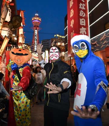 大阪の観光名所・新世界で開かれたハロウィーンイベントで、仮装姿でポーズをとる人たち=26日夕