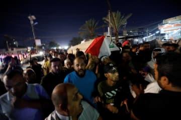 イラク・バグダッドで、死亡した反政府デモ参加者のひつぎを運ぶ人たち=25日(ロイター=共同)