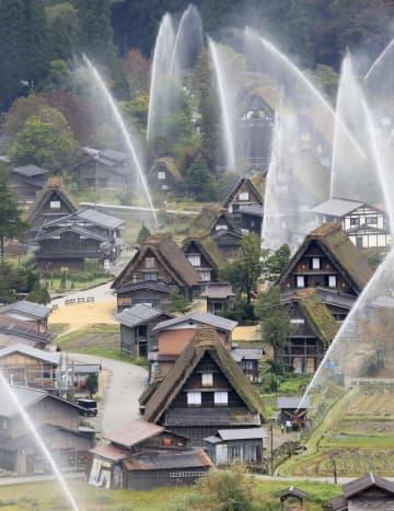 放水訓練で水柱が上がる世界文化遺産の白川郷の合掌造り集落=27日午前、岐阜県白川村