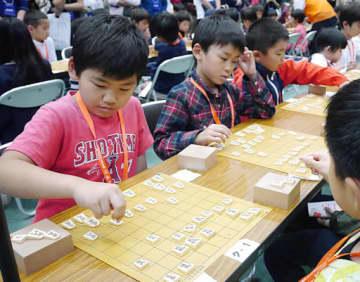 真剣な目つきで対局する子どもたち=26日、大阪市港区の丸善インテックアリーナ大阪