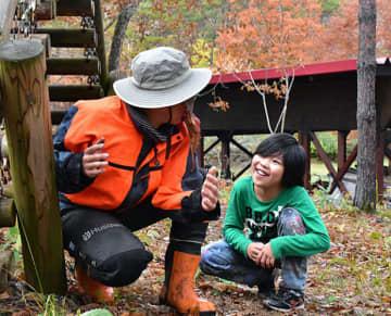 紅葉を楽しみながら、スタッフと交流する参加児童
