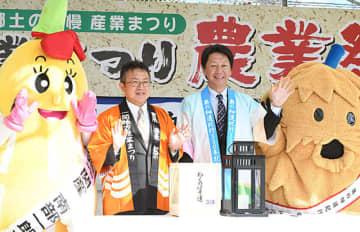俳聖の火(手前の黒い箱)を分け終え、来場者に笑顔で応える高橋邦夫副市長(左から2人目)と菅原浩志課長