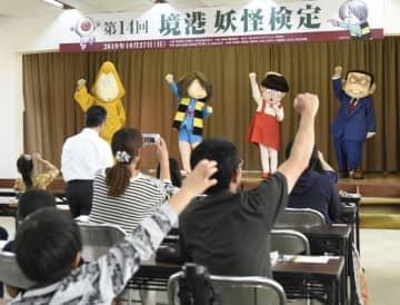 「境港妖怪検定」の試験前に拳を突き上げ気合を入れる受験者ら=27日、鳥取県境港市