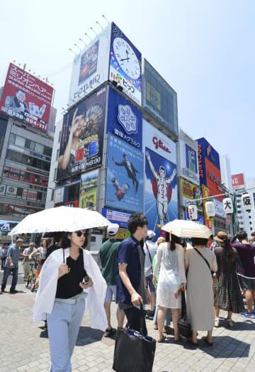 厳しい暑さが続く中、大阪・戎橋で日傘を差して歩く女性ら=2018年7月