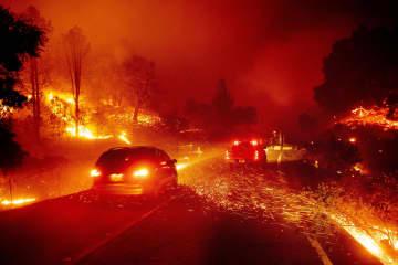 24日、米カリフォルニア州ソノマ郡で発生した山火事で、道路周辺に飛び交う火の粉(AP=共同)