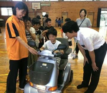 シニアカーに乗ってお年寄りの生活を疑似体験する児童と見守る生徒=大分市の判田小