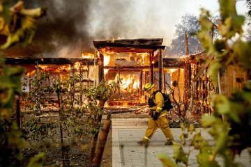 27日、米カリフォルニア州ヒールスバーグで、山火事で燃えさかる住宅の前を歩く消防士(AP=共同)