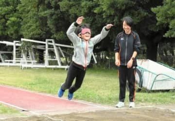 アイマスクを着けて立ち幅跳びを体験する参加者
