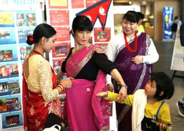 ネパールの民族衣装「サリー」を試着する森さんら(左から2人目)=長崎県庁