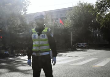 4中総会の会場と見られる建物のそばで警備する警察官=28日、北京(共同)