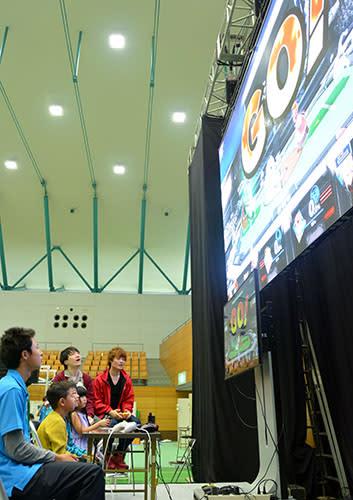 200インチの大画面にeスポーツ選手と来場者の対戦が映し出されたエキシビションマッチ=酒田市国体記念体育館