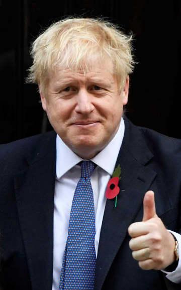 28日、ロンドン市内で撮影に応じるジョンソン英首相(ロイター=共同)