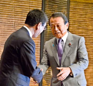 河野防衛相と握手を交わす麻生副総理(右)=28日夜、東京都内