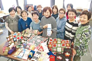 編み上げた作品を前に笑顔を見せる木内さん(中央)ら会員