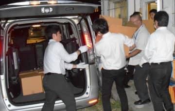 落札業者の会社事務所を家宅捜索し、証拠品を押収する捜査員=28日午後6時50分、うるま市