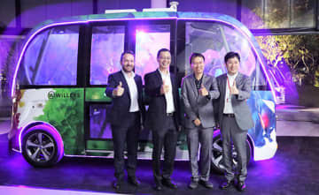 "Willer Inc. CEO Shigetaka Murase (R) and other senior company officials pose in front of an ""Auto Rider"" autonomous driving bus at a seaside park in Singapore on Oct. 23, 2019."