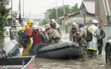 泥水が住宅街を襲い、逃げ遅れた住民を救助するためボートが出動した=八戸市尻内町矢沢地区(1999年10月29日付本紙紙面)