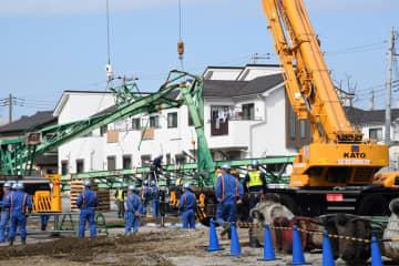 ゴルフ練習場の倒れた鉄柱を撤去する作業員ら=28日午前11時10分ごろ、市原市五井