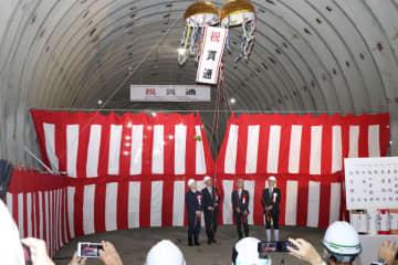 石川、福井両県の県境付近で開かれた加賀トンネルの貫通式で、くす玉を割る関係者=29日午前