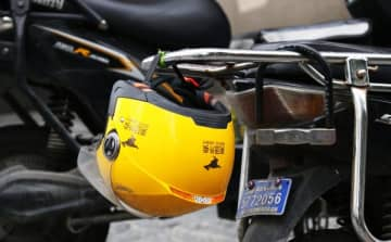 A Meituan helmet hangs on the back of an electric bicycle in Shanghai on March 29, 2019. (Image credit: TechNode/Shi Jiayi)