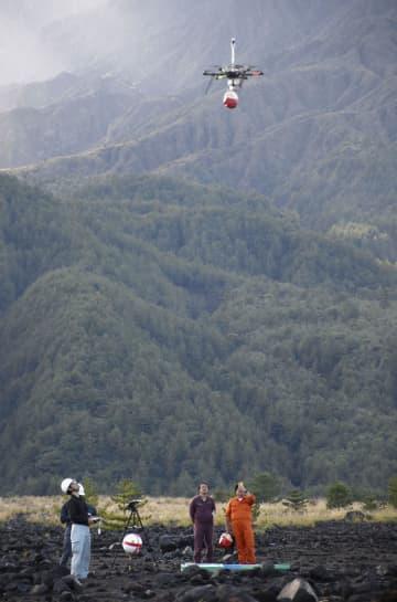 京都大防災研究所と日本気象協会が行った実証実験で、ドローンを飛ばす関係者=29日午後、鹿児島市の桜島