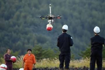 桜島でドローンによる噴石模型投下実験をする京都大学防災研究所や日本気象協会の関係者=鹿児島市黒神町
