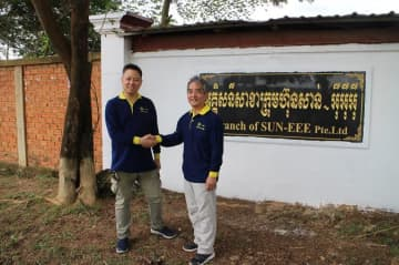Sovarong Leang (L), the founding CEO of Sun Eee Pte. Ltd., shakes hands with Shinichi Imai, president of Greenway Grid Global Pte. Ltd., in front of a Cambodian branch of Sun Eee. (Photo courtesy of Greenway Grid Global)